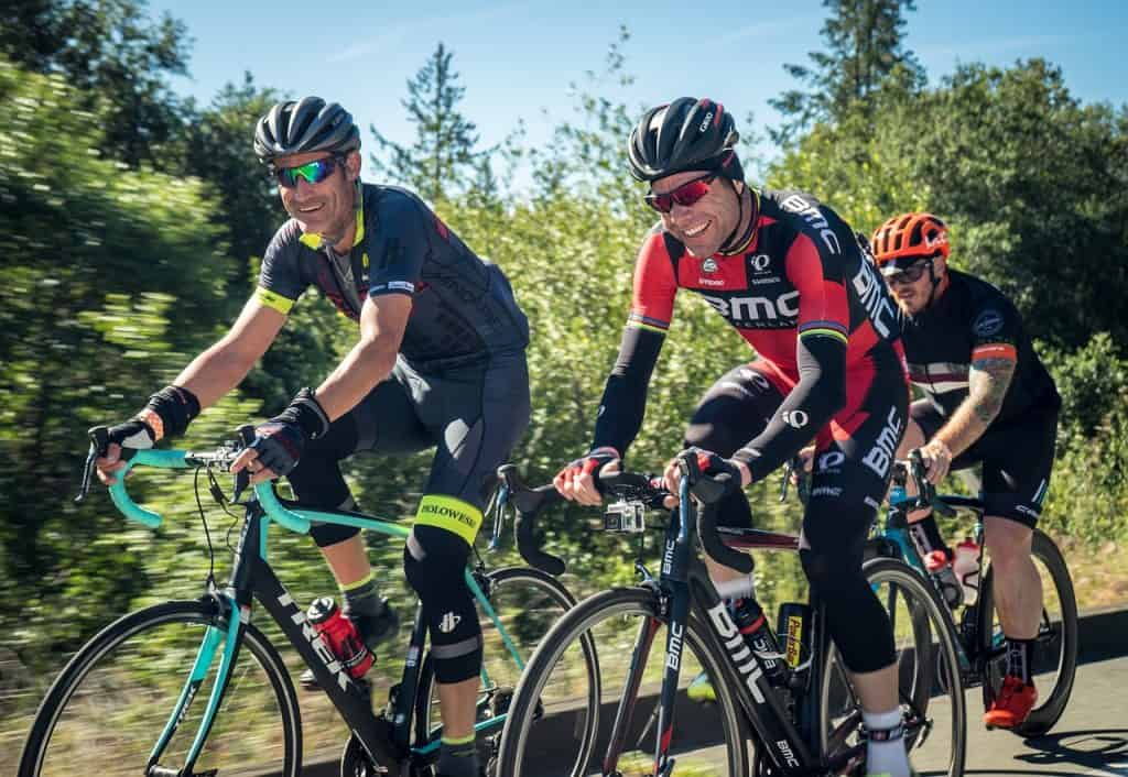 Três homens equipados pedalando na estrada.