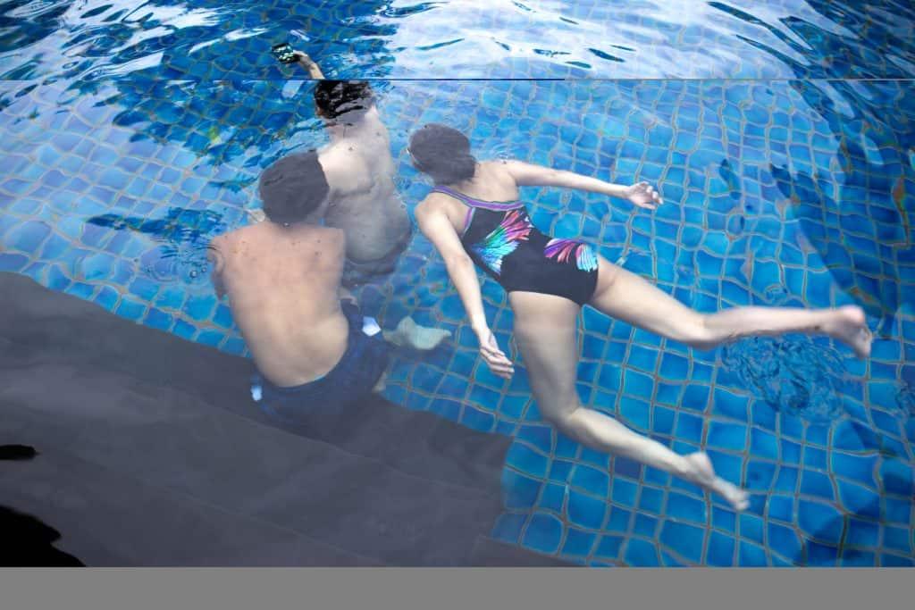 Imagem de três pessoa tirando foto debaixo d'água em piscina.