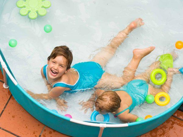Uma criança e um bebê brincam em uma piscina a infantil.