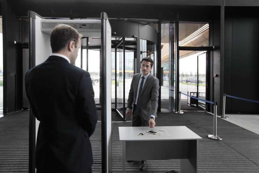 Homem passando pelo detector de metais em um aeroporto.