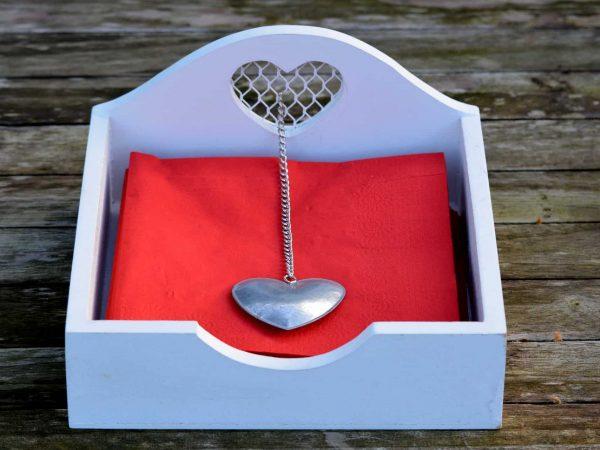 Imagem mostra porta guardanapo horizontal branco, com detalhes em formato de coração e com guardanapos dentro dele. Ele repousa sob uma superfície de madeira gasta.