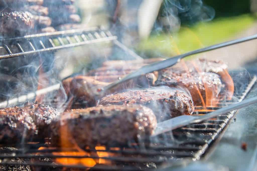 Imagem bem de perto de uma churrasqueira, com vários pedaços de carne vermelha e um pegador de carne.
