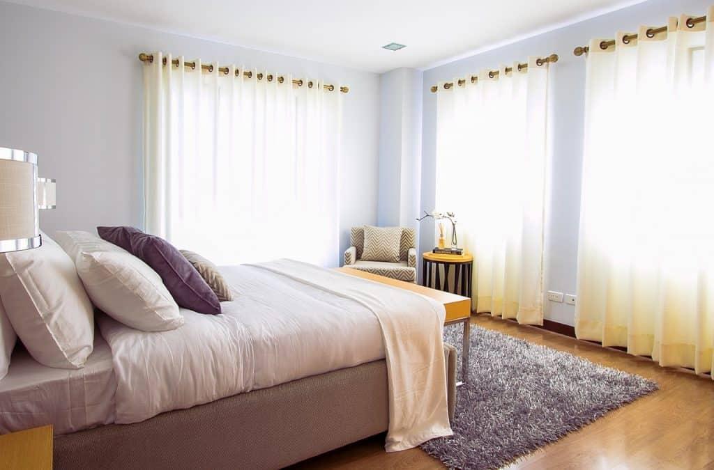 Quarto com janelas amplas e bem iluminado. A cama está arrumada com lençol, edredom, travesseiro e almofadas e aparece na lateral.