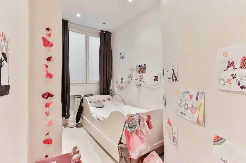 Imagem de quarto de menina com cama com grades de proteção no mesmo padrão do móvel.