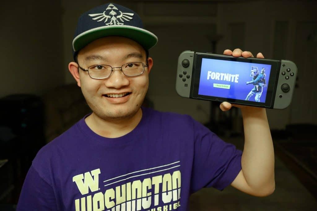 Um adolescente de boné segurando um Nintendo Switch com a mão esquerda.