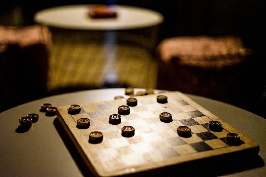 Imagem mostra um tabuleiro e um jogo de damas em andamento.