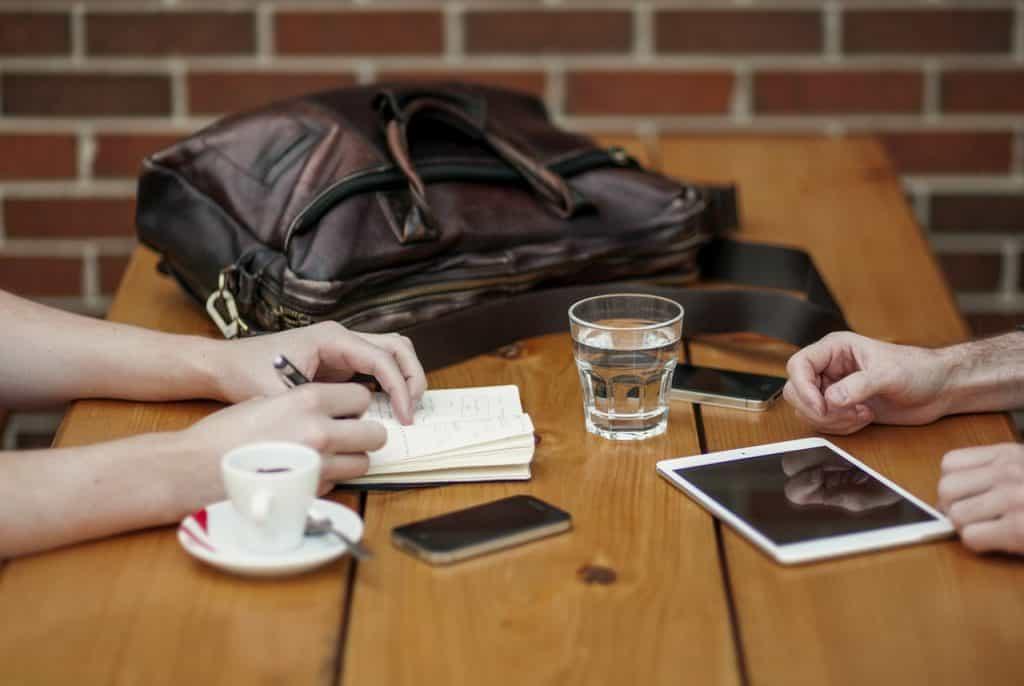 Foto das mãos de duas pessoas que estão sentadas de frente uma para a outra bebendo café, água e anotando coisas.