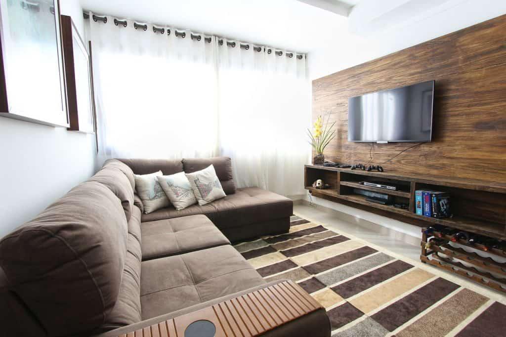 Sala grande com painel para tv marrom.