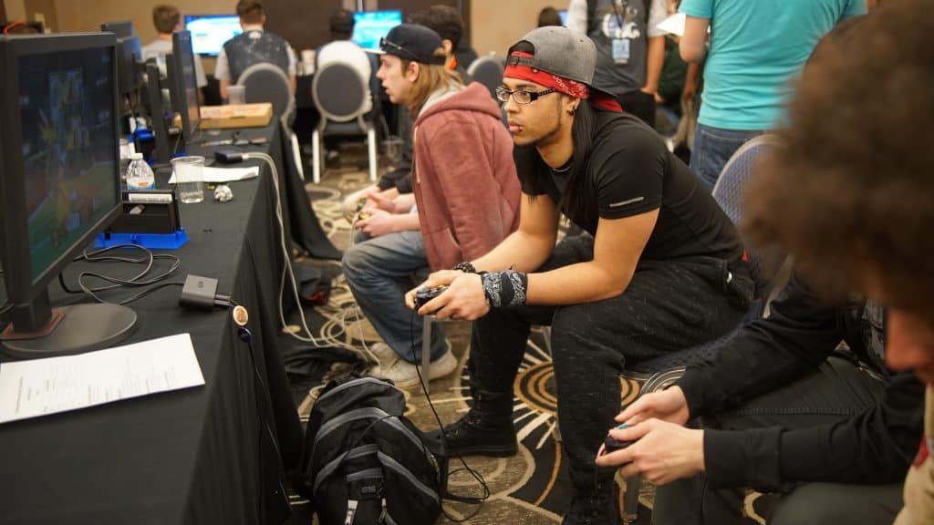 Imagem de sala com várias mesas de video games e pessoas jogando em duplas.