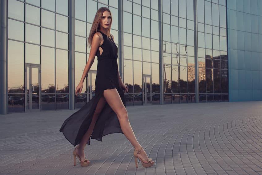 Foto de uma mulher andando na rua com vestido preto e sandália de salto meia pata nude.