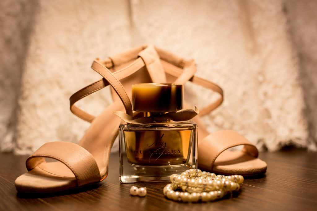 Imagem mostra sandália nude com perfume, brincos e pulseira ao lado.