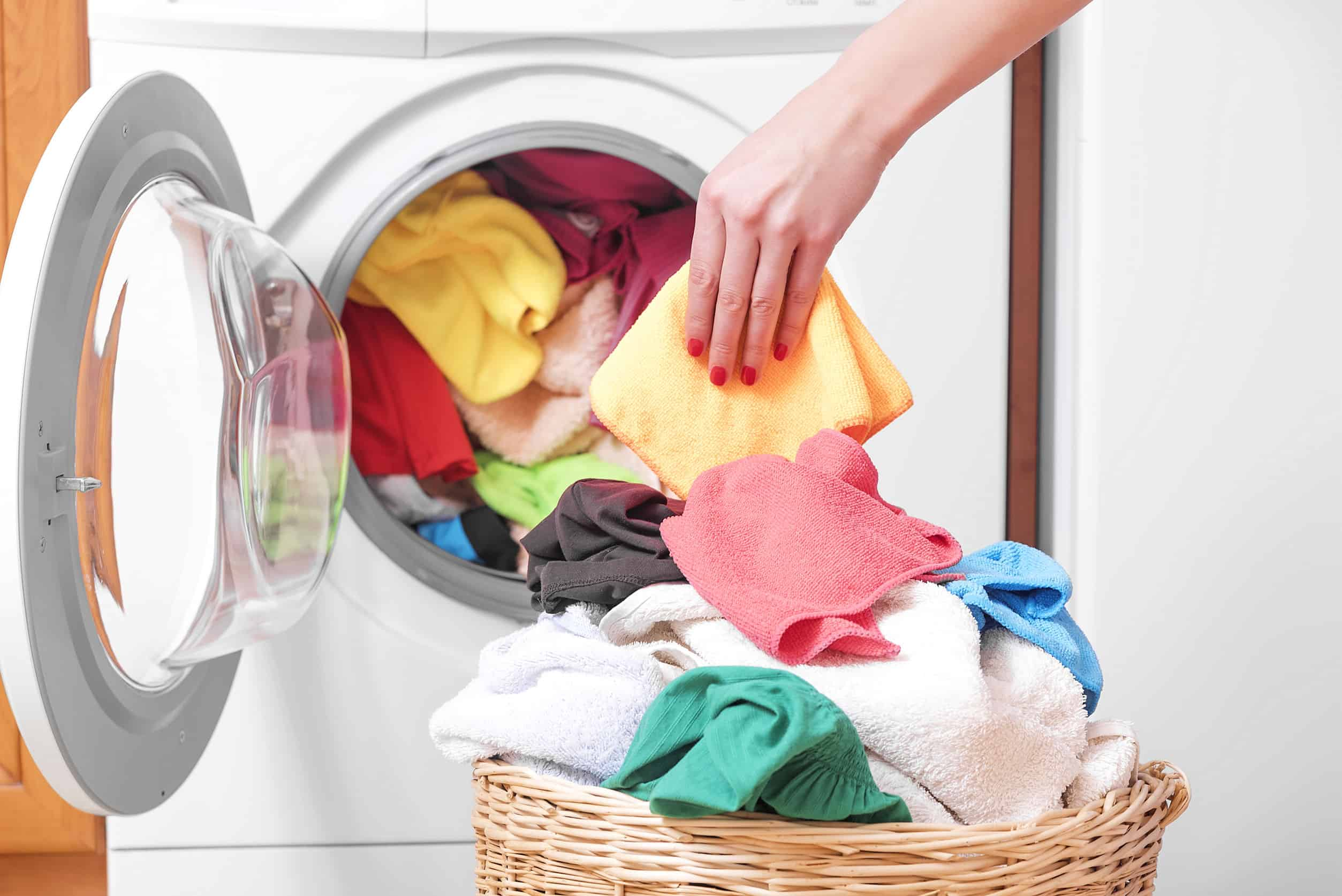 Imagem mostra pessoa tirando roupas secas de secadora de roupas.