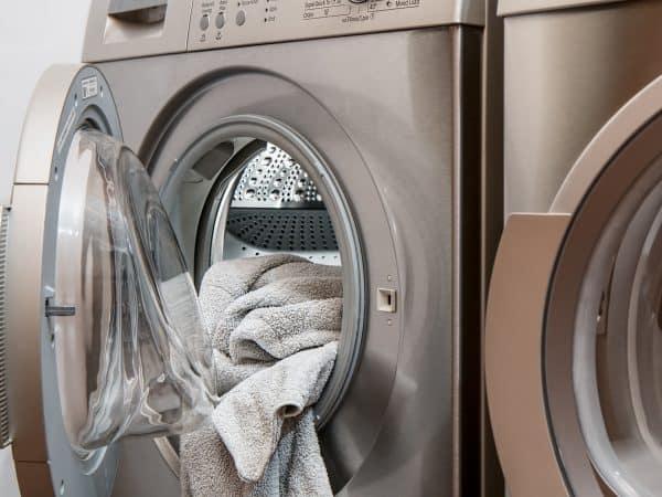 Imagem de uma secadora de roupas aberta, com uma toalha cinza pendurada.