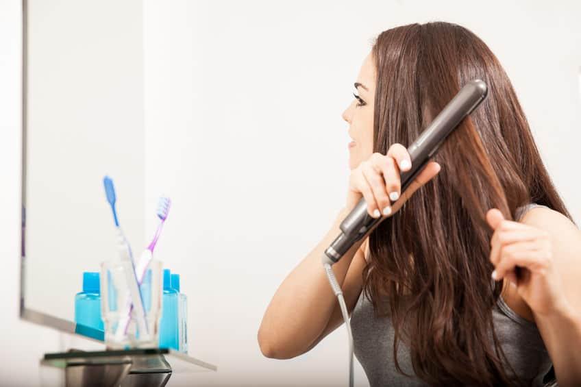 Imagem de uma mulher passando a chapinha no cabelo na frente do espelho do banheiro.