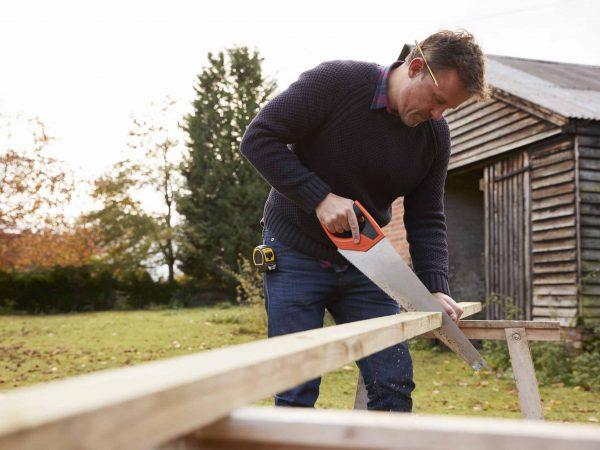 Um homem serrando uma madeira com serrote no jardim, ao ar livre, na frente de uma casa de madeira.