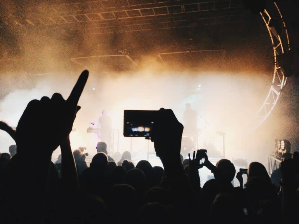 Foto escura que mostra um palco enevoado, com uma banda tocando, e várias pessoas assistindo. Algumas pessoas seguram o celular para filmar ou fotografar.