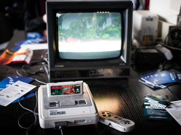 Um Super Nintendo que tem um controle conectado em frente a TV com jogos ao redor.