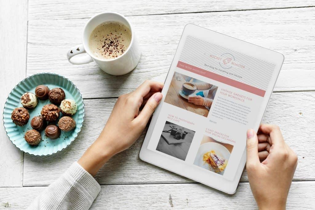 Foto de duas mãos segunda um tablete branco, com uma travessa de bombons ao lado, de uma xícara contendo uma bebida quente.