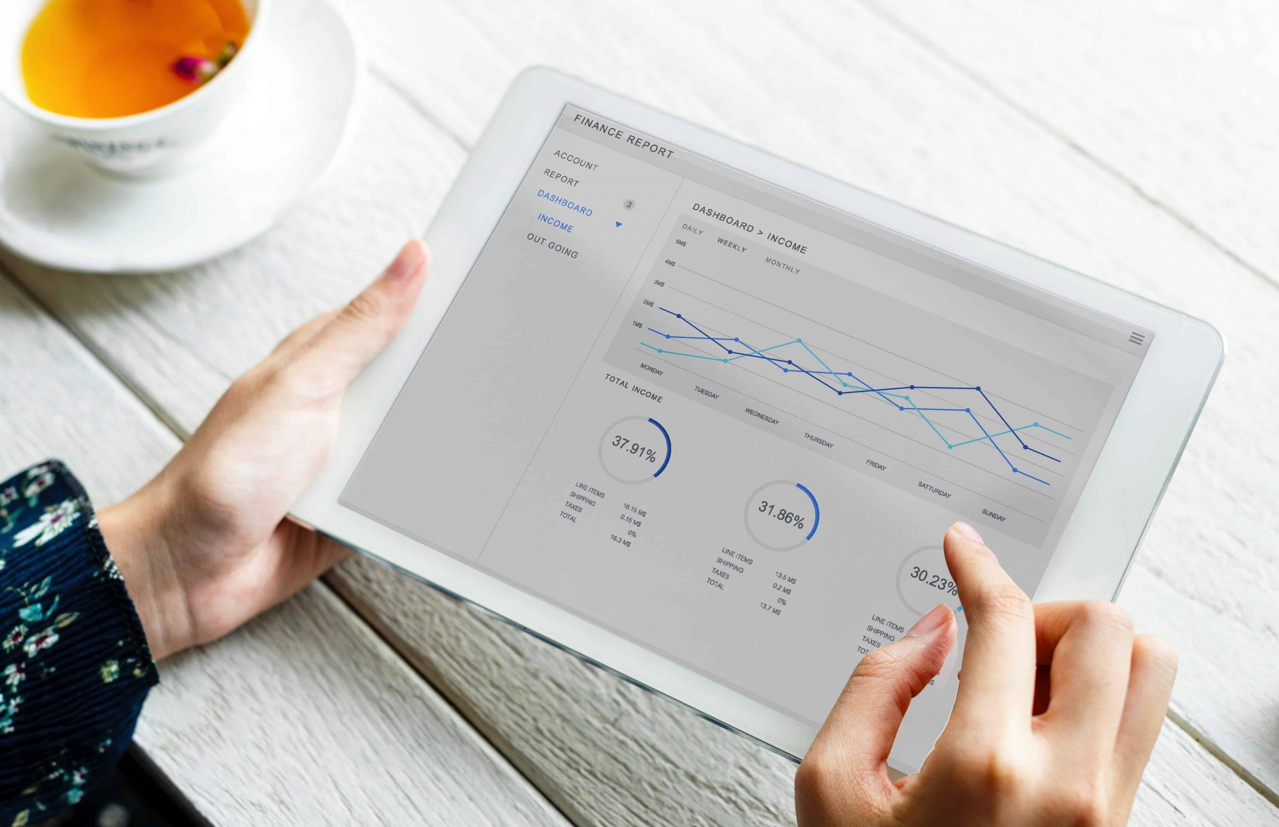 Foto das mãos de uma pessoa segurando um tablet branco, que mostra números e estatísticas. Ao lado, uma xícara com chá em tom alaranjado.