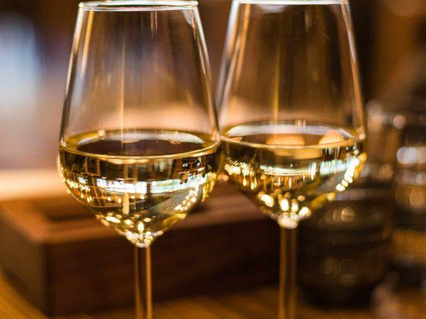 Foto de duas taças, com vinho branco dentro e fundo com blur.