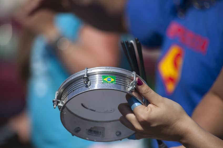 Imagem de close da mão de uma mulher tocando tamborim.