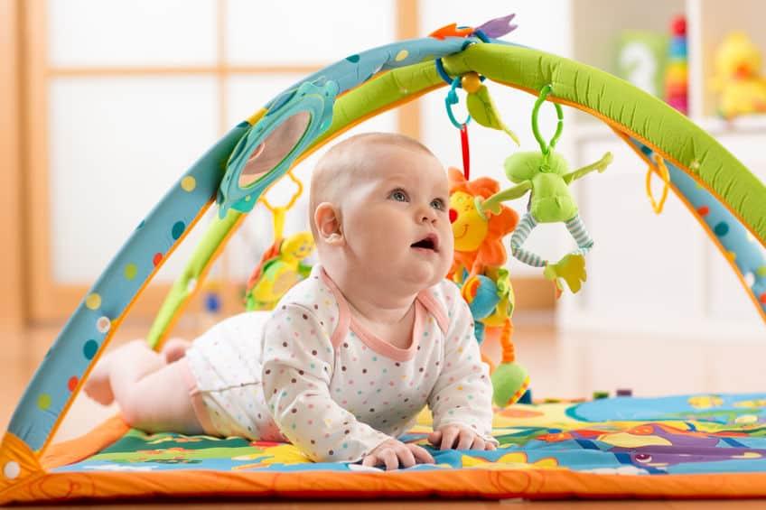 Imagem de bebê olhando para brinquedo em tapete de atividades.