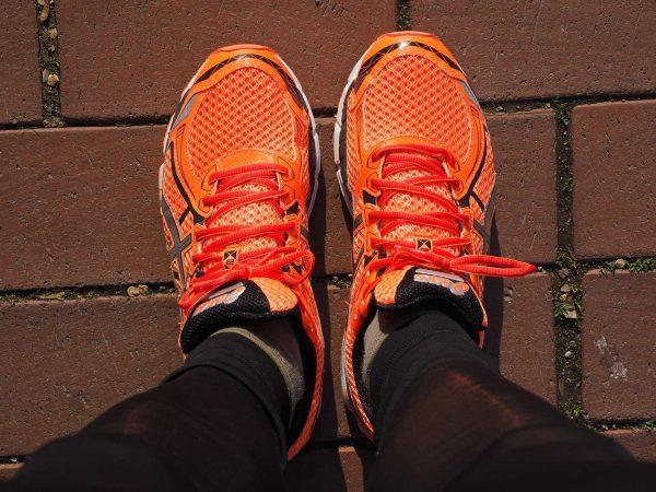 Imagem mostra mulher calçada com tênis de corrida laranja.