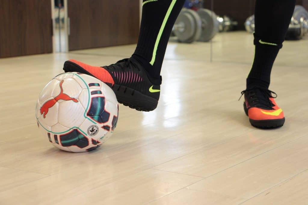 Imagem de tênis e bola de futsal.