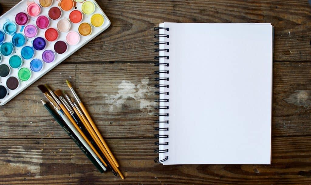 Na foto um caderno com pincéis de pintura e uma paleta de tintas aquarela sobre uma mesa de madeira.