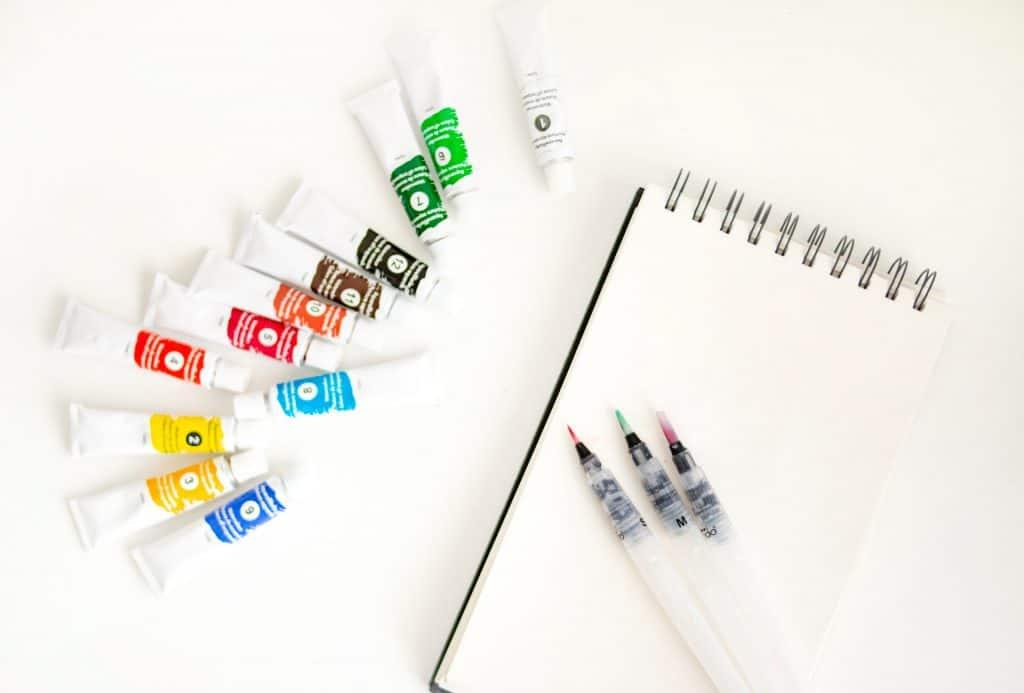 Na foto um caderno com canetas de pintura em cima e ao lado esquerdo diversas bisnagas coloridas de tinta aquarela.