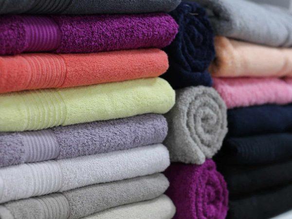 Imagem mostra toalhas de diversas cores dobradas e empilhadas.