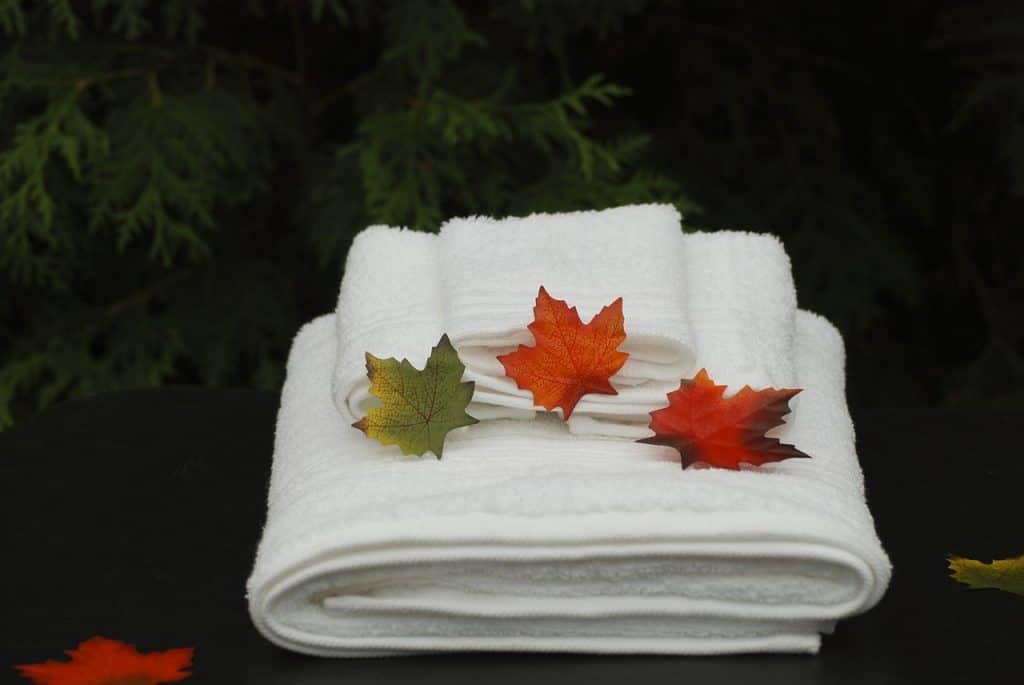 Imagem mostra toalhas brancas empilhadas.