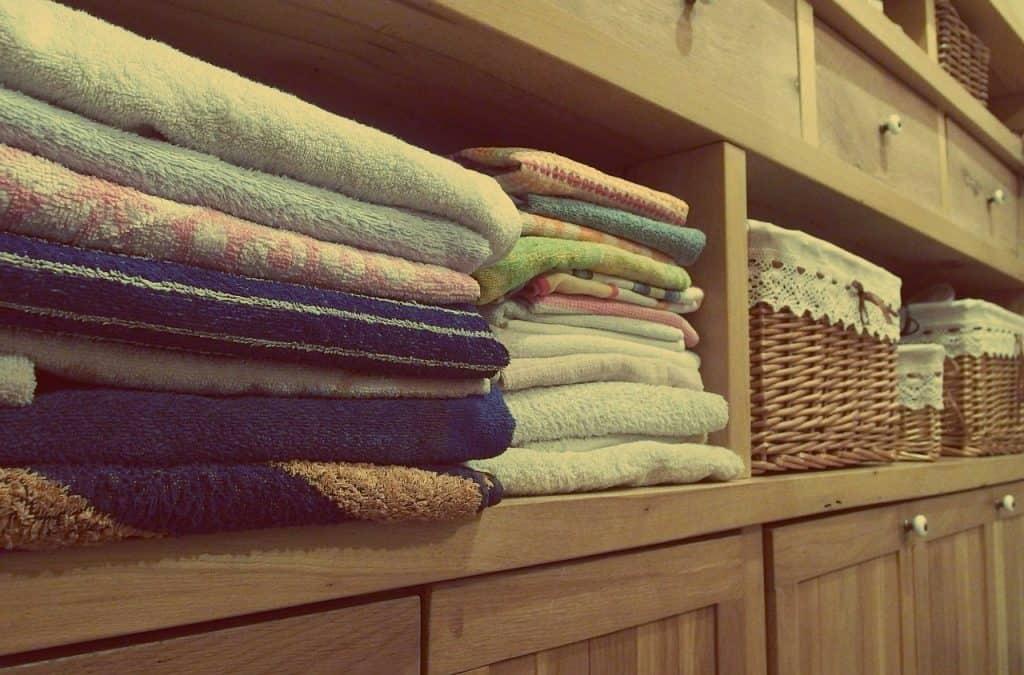 Imagem de toalhas empilhadas dentro de armário.