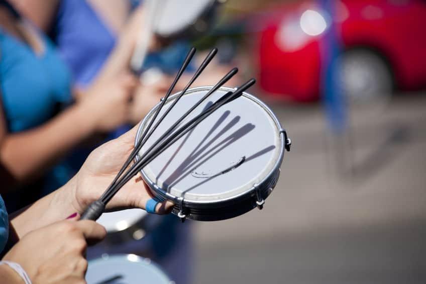 Imagem de pessoa tocando tamborim na rua.