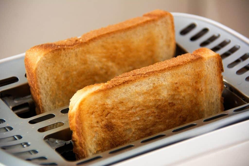 Imagem mostra duas fatias de pães em uma torradeira.