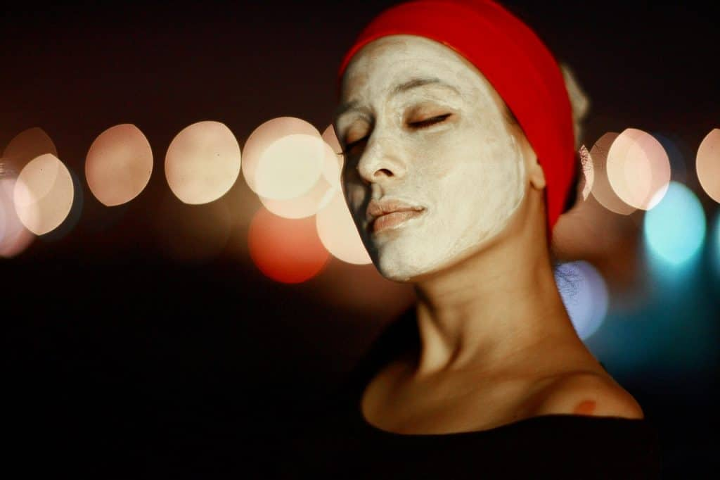 Foto de uma mulher com uma faixa vermelha nos cabelos, olhos fechados e creme no rosto.