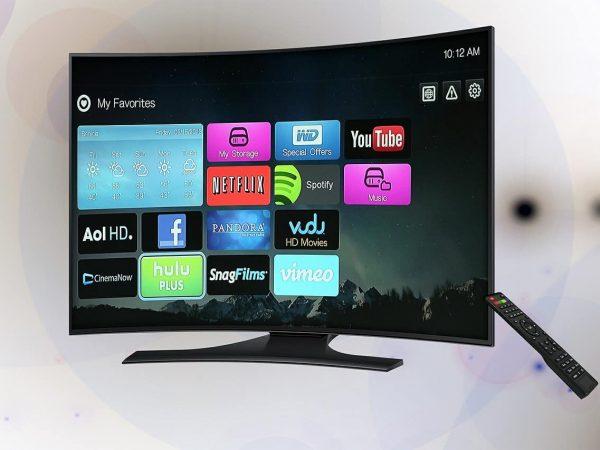 Imagem de uma tv com tela curva e controle ao lado.