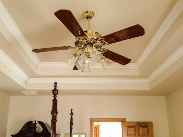 Imagem mostra um modelo clássico de ventilador de teto com iluminação acoplada.