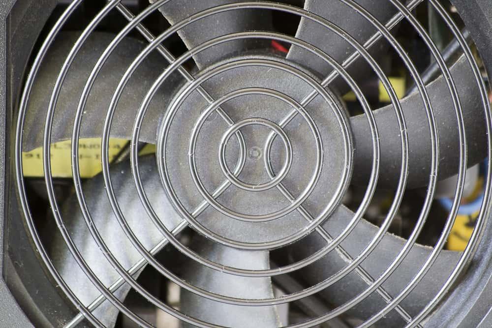 Imagem de grade e folhas de ventilador prateado.