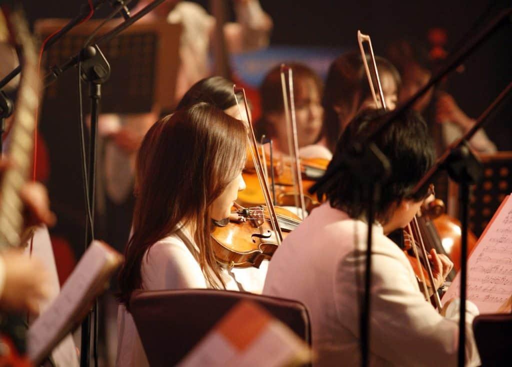 Foto em close de violinistas em orquestra.