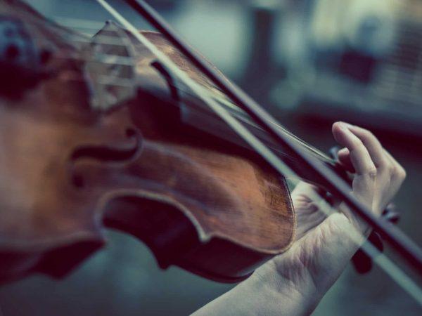 Imagem em close de um violino sendo tocado, aparecendo apenas o arco tocando nas cordas e a mão do violonista, montando o acorde.