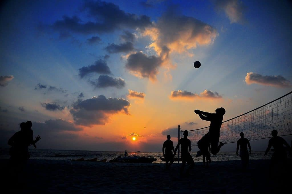 Rede de vôlei em uma praia. O céu está azul e, ao fundo, há algumas pessoas e casas.