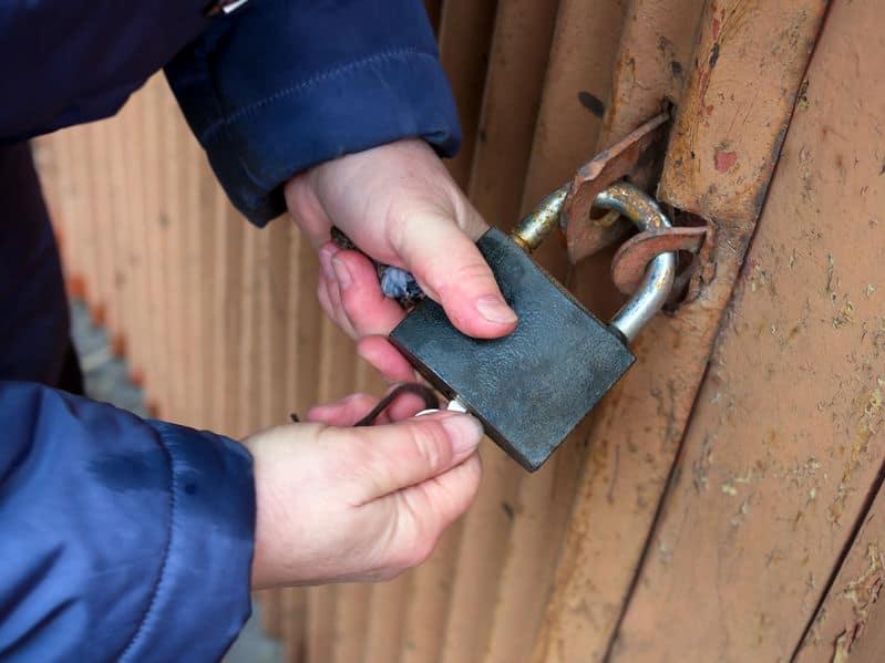 Mão abrindo cadeado com chave.