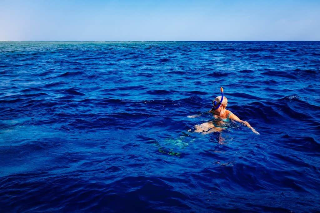 Na foto uma mulher no meio do mar com um máscara de mergulho e um snorkel.