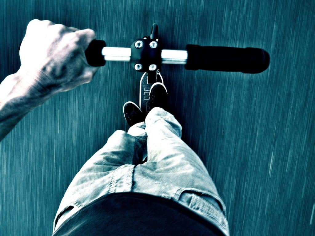 Imagem mostra um homem pilotando um patinete elétrico e o ângulo superior da foto destaca a velocidade.