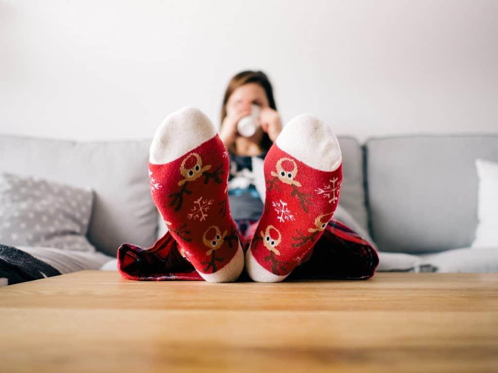 Imagem de pessoa em sofá tomando café apoiando os pés na mesa de centro.