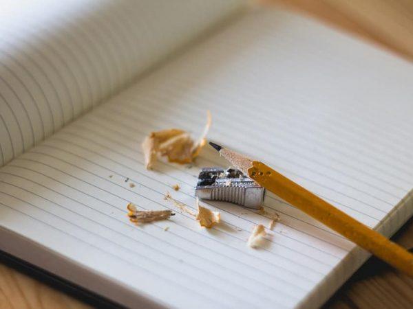 Lápis com ponta feita em cima do caderno.