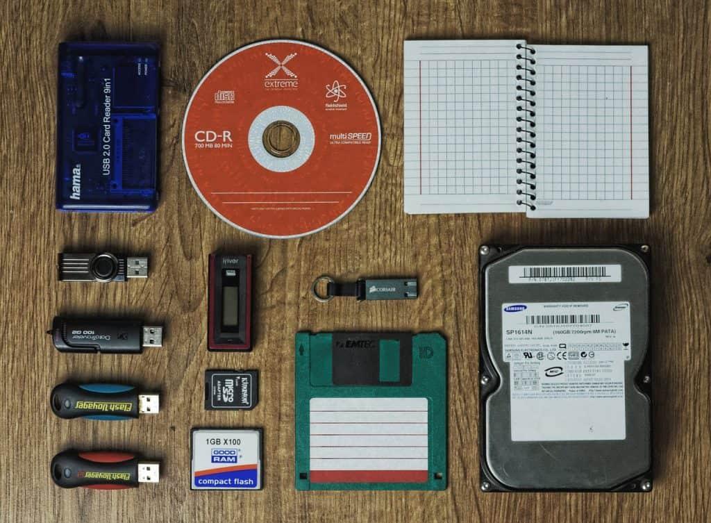 Imagem mostra diferentes tipos de dispositivos de memória externa: disquete, CD, pen drives, cartões de memória e HDs externos.