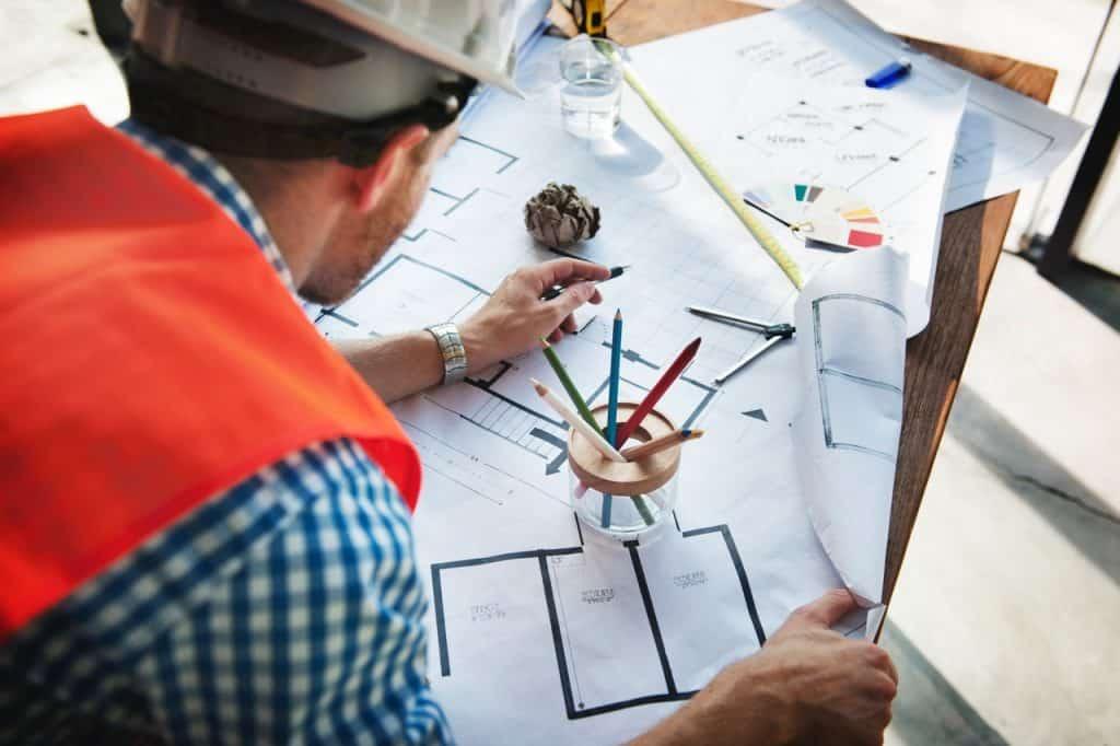 Na foto um engenheiro debruçado sobre alguns desenhos.