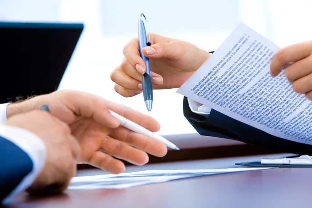 Imagem de homens de negócios segurando canetas esferográficas e documentos.
